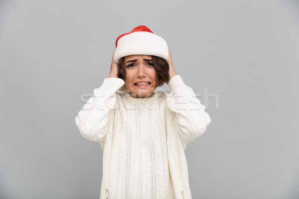 Portrait of a confused puzzled girl in christmas hat Stock photo © deandrobot