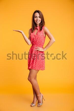 Portret jonge glimlachende vrouw rode jurk tonen Stockfoto © deandrobot