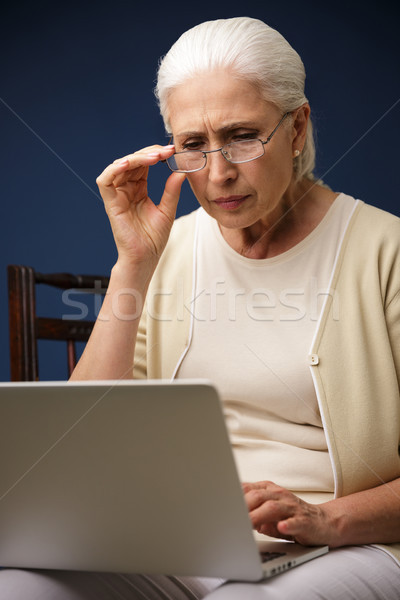 Serious old woman using laptop computer. Looking aside. Stock photo © deandrobot