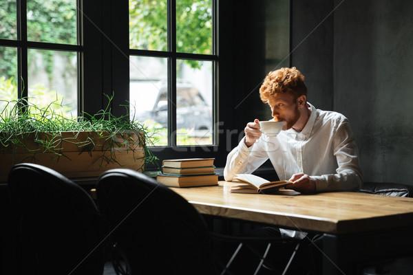 Photo of handsome readhead bearded man drinkin coffee in city ca Stock photo © deandrobot