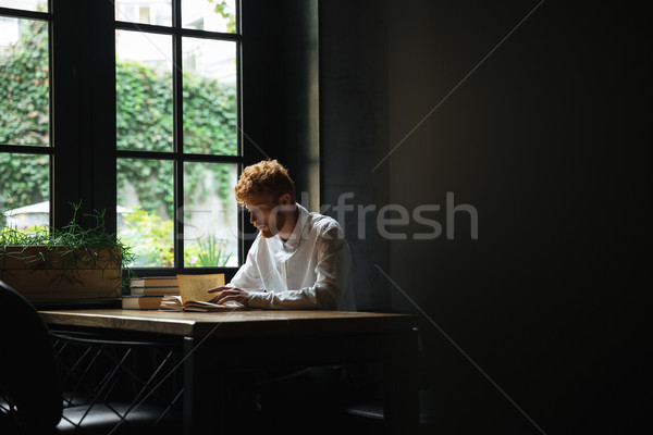 Photo of young readhead bearded man reading a book in cafeteria Stock photo © deandrobot