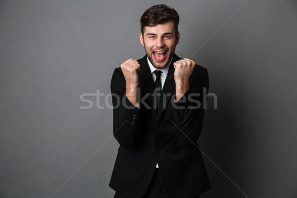 Close-up photo of happy attractive man in classic suit showing w Stock photo © deandrobot