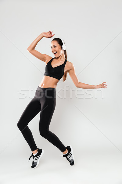 Full length portrait of a happy asian fitness woman Stock photo © deandrobot