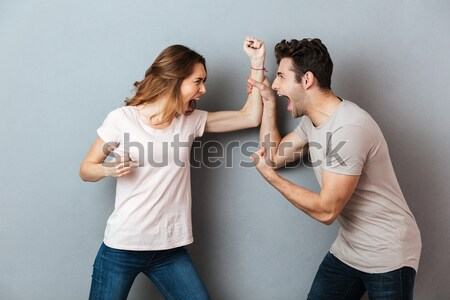 Handsome young man showing biceps to his amazed girlfriend Stock photo © deandrobot