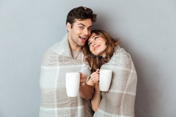 Stock photo: Portrait of a happy young couple standing wrapped in blanket