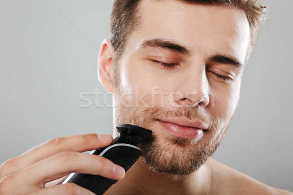 Headshot of caucasian pleased guy 30s being undressed at bathroo Stock photo © deandrobot