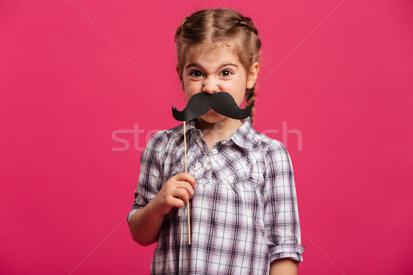Angry funny little girl child holding fake moustache. Stock photo © deandrobot
