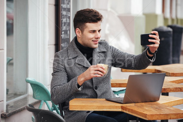 Image of cheerful brunette man making selfie or skyping while re Stock photo © deandrobot