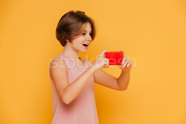 Happy modern girl using smartphone for recording video isolated Stock photo © deandrobot