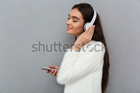 Widok z boku uśmiechnięty brunetka kobieta sweter słuchawki Zdjęcia stock © deandrobot