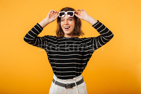 Portrait of a cheerful girl in sunglasses winking Stock photo © deandrobot