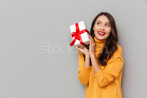 Pleased woman in sweater holding gift box and looking away Stock photo © deandrobot