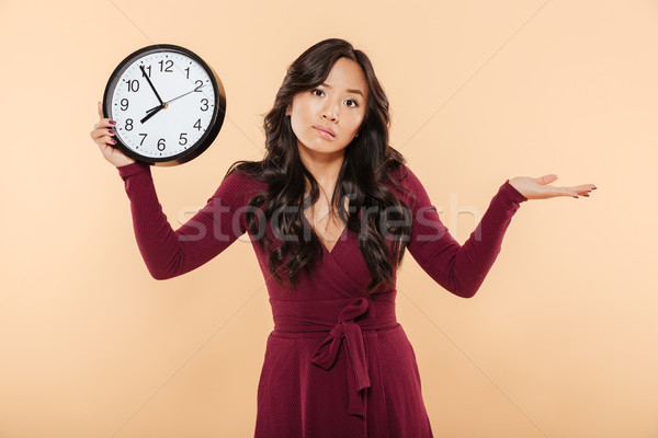 Cute brunette woman with curly long hair holding clock showing n Stock photo © deandrobot