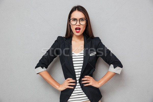 Displeased asian business woman in eyeglasses with arms on hips Stock photo © deandrobot