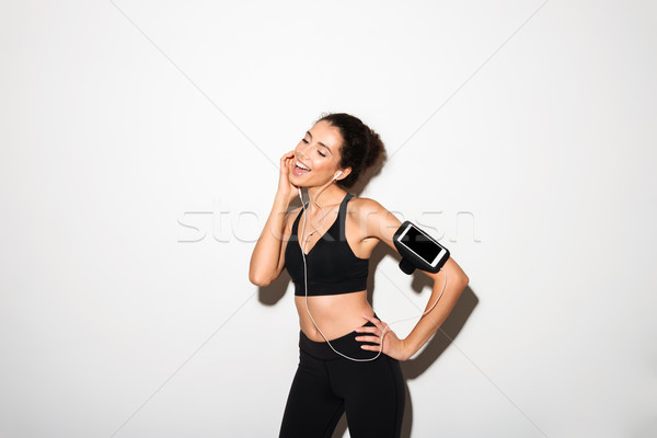 Pleased curly brunette fitness woman listening music by smartphone Stock photo © deandrobot