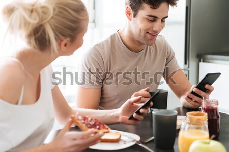 Young beautiful couple sitting in kitchen and have breakfast Stock photo © deandrobot