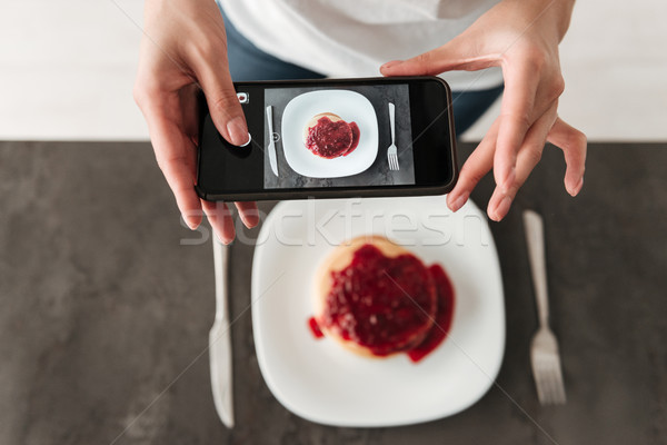 Cropped photo of woman make photo of pancakes by phone. Stock photo © deandrobot