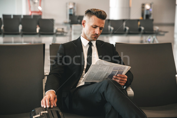 Confident businessman reading newspaper Stock photo © deandrobot