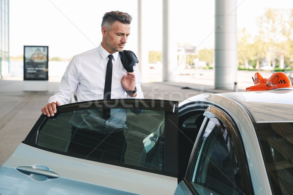 Successful mature businessman getting in taxi Stock photo © deandrobot
