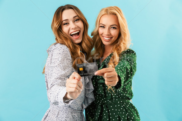Two joyful women in dresses showing credit card Stock photo © deandrobot
