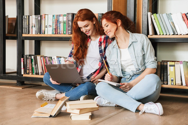 Two smiling teenage girls sitting on a floor at the bookshelf Stock photo © deandrobot