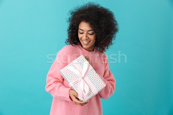 Portrait of joyous woman 20s with afro hairdo holding gift box a Stock photo © deandrobot