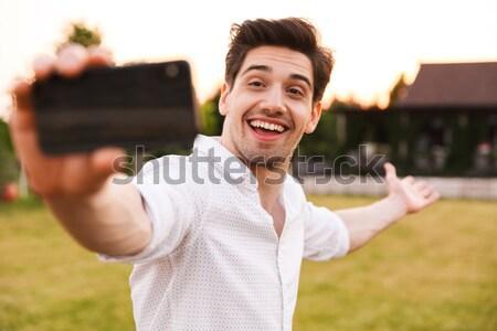 Obraz szczęśliwy młody człowiek biały shirt Zdjęcia stock © deandrobot