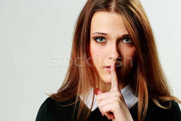 Closeup portrait of a young woman with silence sign isolated on gray background Stock photo © deandrobot