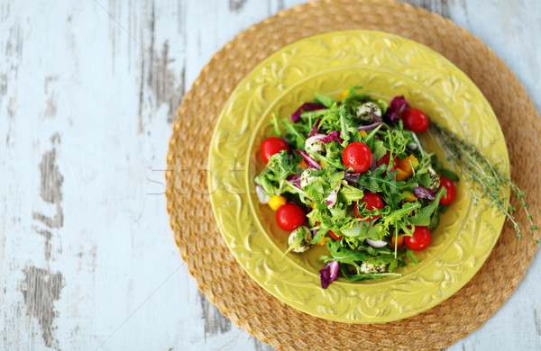 Fresh salad served on vintage plate. View from above Stock photo © deandrobot