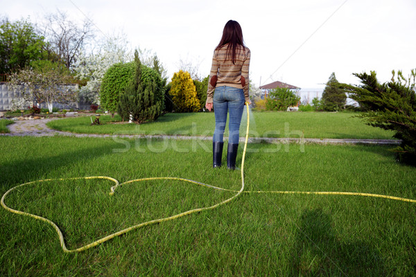Back view portrait of a woman is watering grass in her garden Stock photo © deandrobot