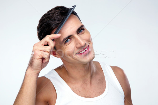Happy man combing his hair over gray background Stock photo © deandrobot