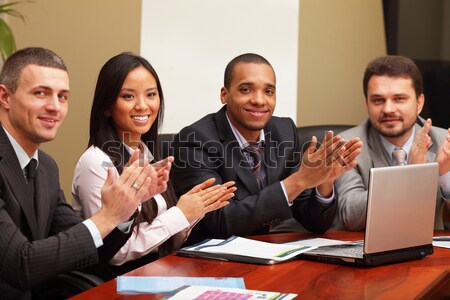 Multi ethnic business group greets somebody with clapping and smiling. Focus on woman Stock photo © deandrobot