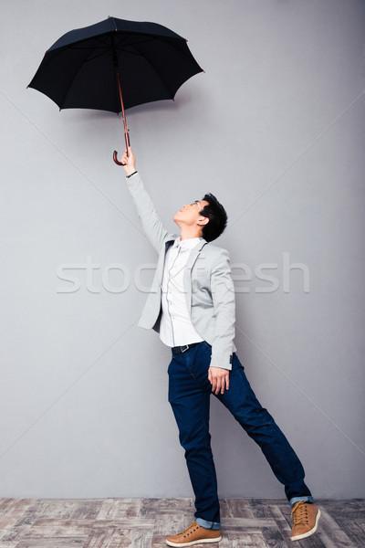 Young man holding umbrella  Stock photo © deandrobot
