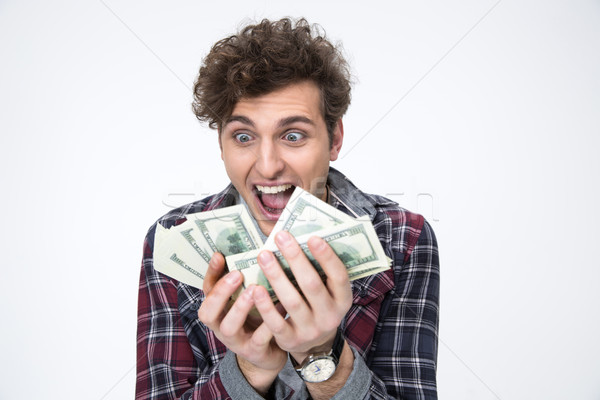 Portrait of a smiling young man holding bills of dollars Stock photo © deandrobot