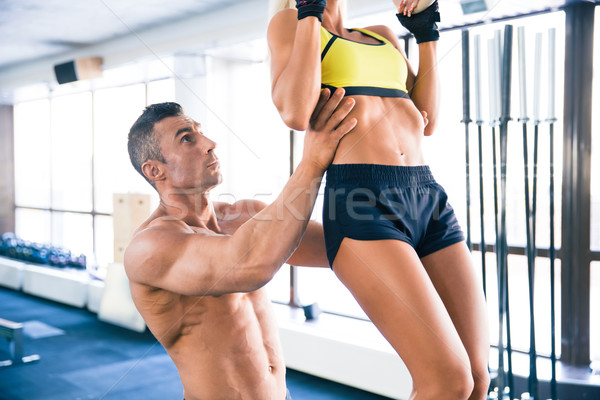 Sporty woman pull-up in gym Stock photo © deandrobot