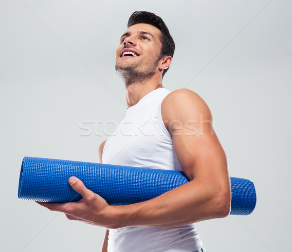 Portrait of a fitness man with yoga mat Stock photo © deandrobot