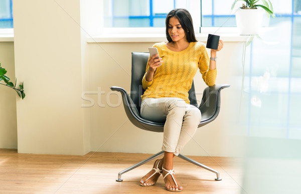 Businesswoman sitting on office chair Stock photo © deandrobot