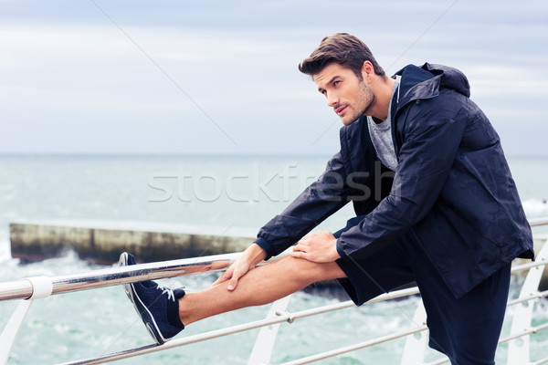 Sportsman stretching legs outdoors  Stock photo © deandrobot