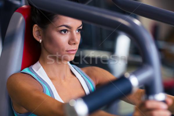 Woman workout on exercises machine Stock photo © deandrobot