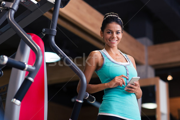 Sports woman standing with smartphone  Stock photo © deandrobot
