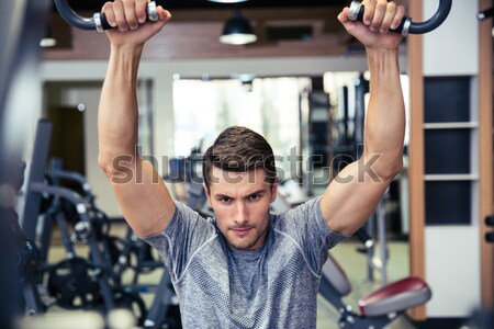 Bodybuilder doing exercise on a fitness machine Stock photo © deandrobot