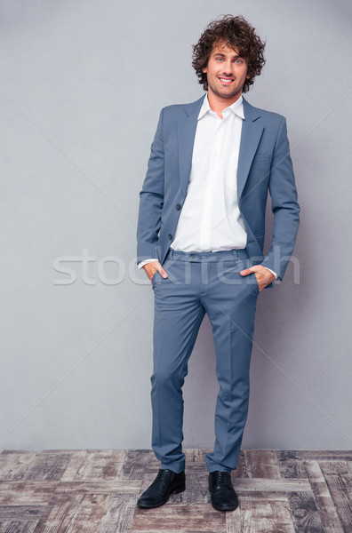 Mutlu işadamı kıvırcık saçlı tam uzunlukta portre ayakta Stok fotoğraf © deandrobot