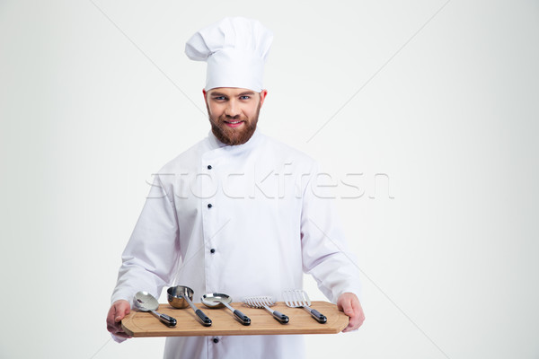 Chef cook holding wooden chopping board with spoons  Stock photo © deandrobot