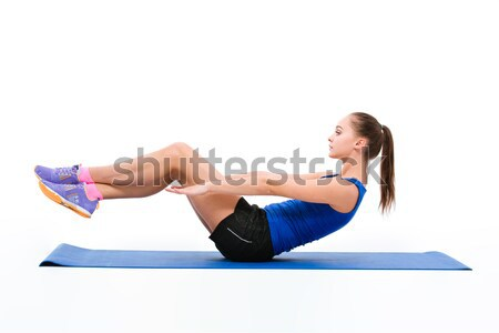 Young sportswoman in sportwear doing exercises Stock photo © deandrobot