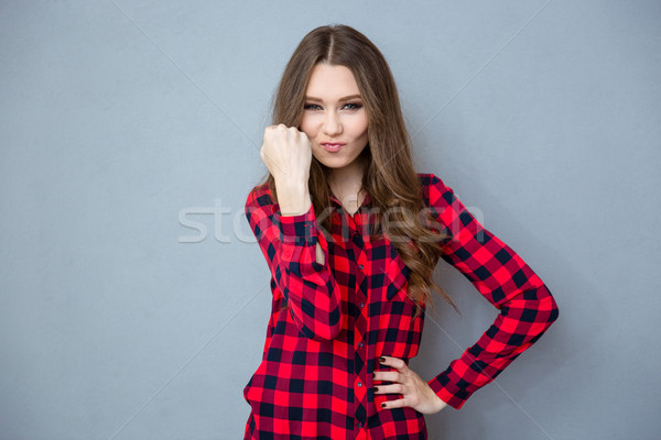 Wicked girl thritting with fist Stock photo © deandrobot
