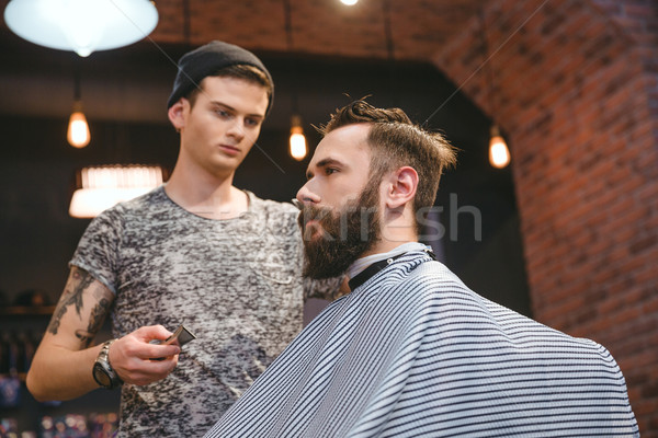 Concentrated hairdresser making haircut to bearded handsome man at barbershop Stock photo © deandrobot