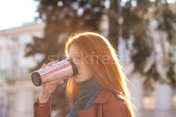 Beautiful redhead lady drinking coffee from tumbler Stock photo © deandrobot