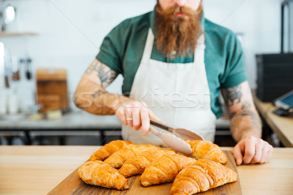 Young man barista with beard taking croissant using tongs Stock photo © deandrobot