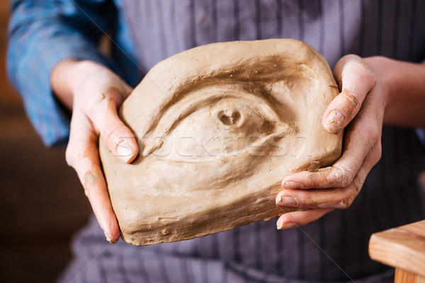 Creative sculpture holded by hands of young woman potter  Stock photo © deandrobot