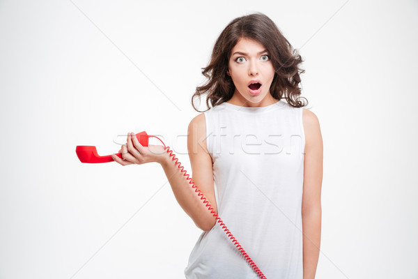 Shocked woman holding phone tube Stock photo © deandrobot